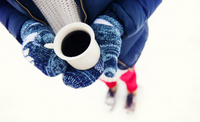 Girl in snow holding a coffee cup