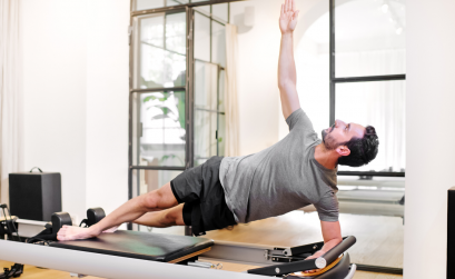 Man on Pilates reformer performing side plank