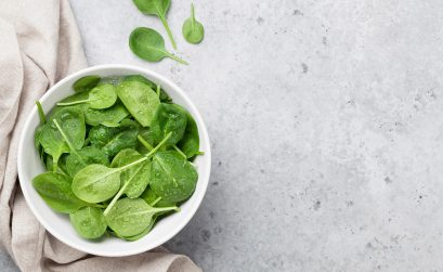 Image of a bowl of baby spinach on a granite countertop.