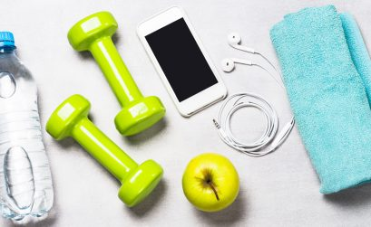 Dumbbells, measuring tape, water and smartphone top view. Fitness concept and healthy lifestyle.