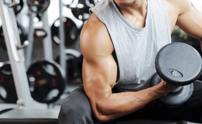 Fit strong man doing biceps curl in gym