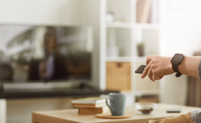Person holding a remote and pointing it at a television
