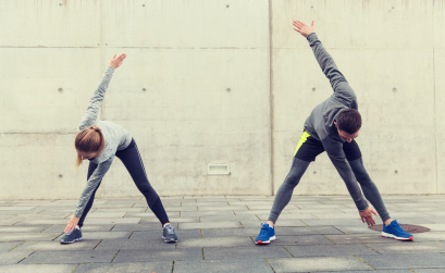 Man and woman outside in running gear stretching