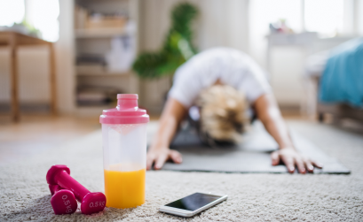 Woman stretching on the floor of her living room with weights and phone nearby.