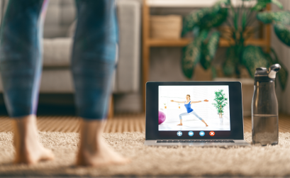 woman with ipad watching yoga class at home
