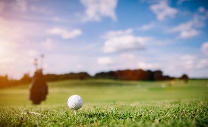 White golf ball on a green grass. Golf course. Summer luxury activities.