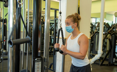 Woman exercising on a piece of gym equipment wearing a face mask.