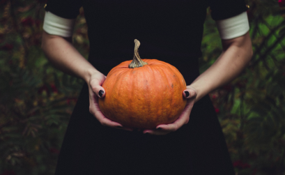 Girl wearing black dress holding a pumpkin