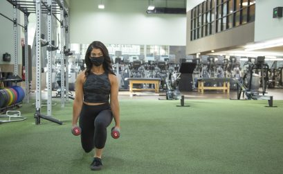 Woman holding dumbbells and performing a lunge at the gym.