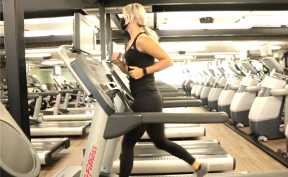 Woman running on treadmill wearing a mask