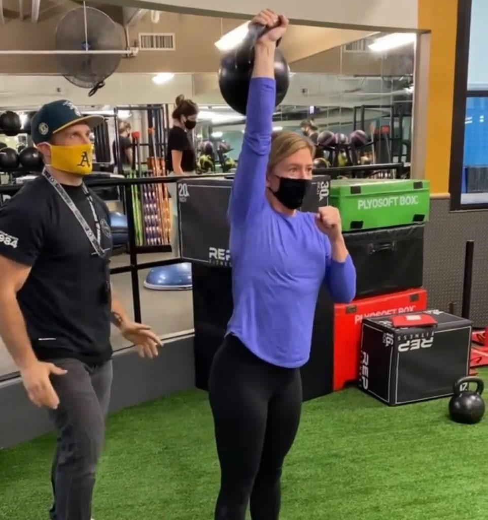 FFC Gold Coast Member Kelly lifting a 48 kg (105 lb) KB over her head.