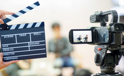Photo of clapboard and digital camera in front of two people sitting