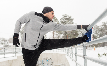 Man in his 30s stretching outside in the snow after a run