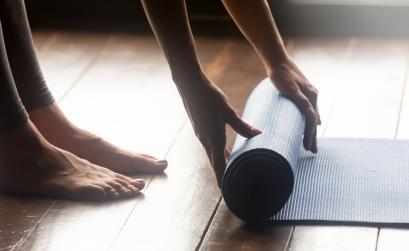 Woman unrolling yoga mat on floor