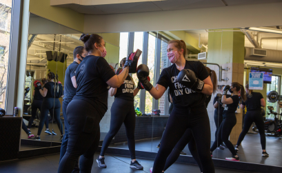 Two women participating in a small group boxing class at a gym